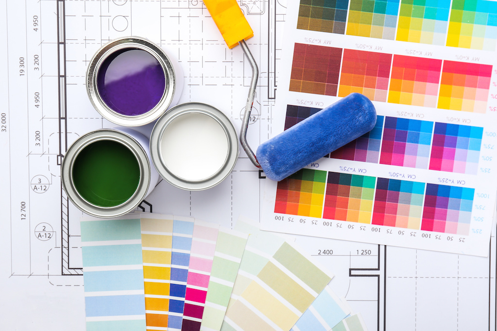Cans of paint with roller, palette samples and house plan
